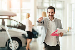 Salesperson working at car dealership Royalty Free Stock Image