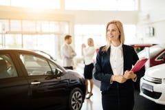 Salesperson working at car dealership. Elegant salesperson working at car dealership royalty free stock images