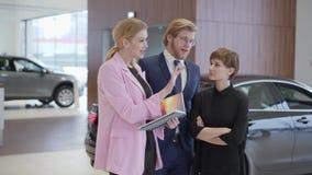 Salesswoman en la chaqueta rosada que muestra la información en libro a los clientes La dependienta profesional ayuda al hombre y almacen de metraje de vídeo