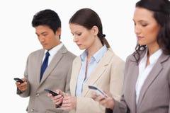 Salesteam som ser deras mobiltelefoner Fotografering för Bildbyråer