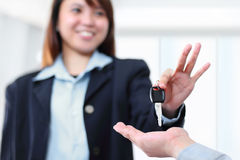 Saleswoman. Young saleswoman handing a car key to a customer.Focus on the key stock photography