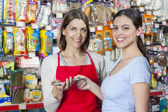 Saleswoman Accepting Card Payment From Female Customer In Pet St Stock Photos