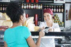 Saleswoman Accepting Payment From Customer In Cheese Shop Stock Images