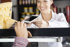 Saleswoman Accepting Payment From Customer Through Credit Card Royalty Free Stock Photos
