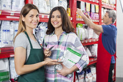 Saleswoman Accepting Payment From Customer In Pet Shop. Portrait of saleswoman accepting credit card payment from customer in pet shop with colleague working in stock photo