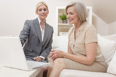 Saleswoman Advising Senior Woman Laptop Computer. A young saleswomen showing a senior women medical insurance or pension information on a laptop computer Stock Photos