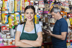 Saleswoman With Arms Crossed Standing While Customer Selecting P. Portrait of confident saleswoman with arms crossed standing while customer selecting product in royalty free stock photo