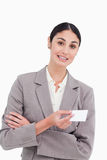 Saleswoman with arms folded and business card Royalty Free Stock Photography