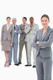 Saleswoman with arms folded and her team behind her Royalty Free Stock Images