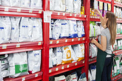 Saleswoman Arranging Food Packages In Pet Store Stock Image