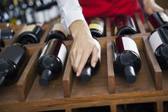 Saleswoman Arranging Wine Bottles In Rack. Cropped image of mid adult saleswoman arranging wine bottles in rack at shop royalty free stock image