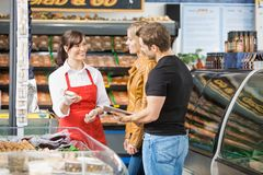 Saleswoman Assisting Couple In Buying Meat Stock Images