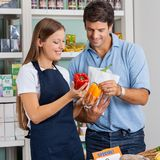 Saleswoman Assisting Male Customer At Grocery Stock Image