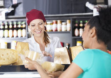 Saleswoman Assisting Young Customer In Buying Cheese. Happy saleswoman assisting young customer in buying cheese at grocery store stock photos