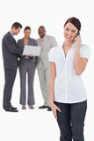 Saleswoman with associates behind her on the phone Stock Photography
