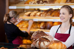 Saleswoman in bakery in front of shelves. Saleswoman in bakery with bread in her hands in front of shelves royalty free stock photo