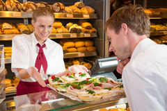 Saleswoman in bakery presenting sandwiches to customer Stock Images