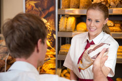 Saleswoman in bakery selling bread to customer Royalty Free Stock Images
