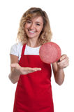 Saleswoman with blond hair presenting italian salami Stock Photos