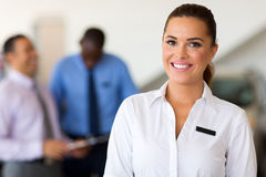 Saleswoman car dealership. Beautiful caucasian saleswoman standing at car dealership stock image