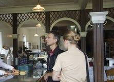 Saleswoman che sposta le torte per un cliente Immagini Stock Libere da Diritti