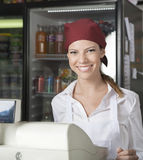Saleswoman At Checkout Counter In Grocery Store Royalty Free Stock Images