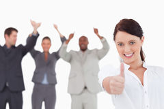 Saleswoman with cheering colleagues giving thumb up Stock Photo