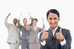 Saleswoman with cheering team behind her giving approval Royalty Free Stock Photography