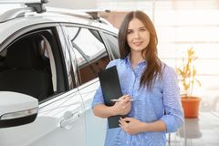 Saleswoman with clipboard in salon. Buying new car royalty free stock photos