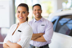 Saleswoman with co-worker. Pretty young saleswoman with co-worker on background stock photos