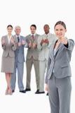 Saleswoman com o polegar ascendente e a sua equipe atrás dela Fotografia de Stock Royalty Free