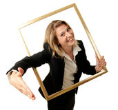 Saleswoman contract. A young businesswoman offering her hand to conclude a contract through a pictureframe Royalty Free Stock Image