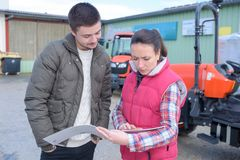 Saleswoman convincing young famrer to buy new agricultural machinery. Industrial royalty free stock photo