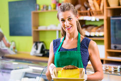 Saleswoman at counter offering cheese Royalty Free Stock Images