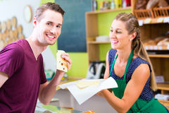Saleswoman at counter offering cheese Royalty Free Stock Photography