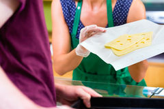 Saleswoman at counter offering cheese Stock Image
