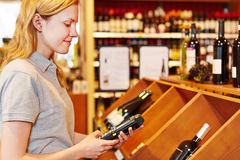 Saleswoman counting wine with data. Saleswoman counting wine bottles with mobile data registration terminal stock photos