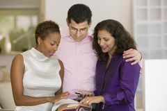 Saleswoman and Couple Examining Fabric Swatches in furniture store front view Stock Photo