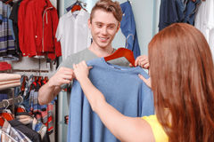 Saleswoman and customer choose clothes. Amazing color. Male shopper and a saleswoman looking with excitement at a shirt at clothing rack in fashionable boutique Stock Photography