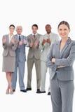 Saleswoman de sorriso com os braços dobrados e sua equipe atrás dela Imagem de Stock Royalty Free