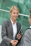 Saleswoman discussing and handshaking partner Stock Images