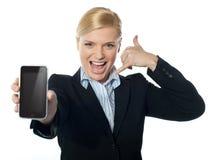 Saleswoman displaying new iphone to camera Stock Image