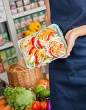 Saleswoman Displaying Packed Chopped Vegetables Stock Image