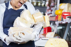 Saleswoman Dropping Stack Of Cheese In Shop Stock Photo