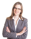 Saleswoman with eyeglasses in a grey jacket looking at camera Royalty Free Stock Image