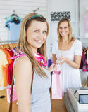 Saleswoman and female customer at the checkout. Both smiling at the camera Royalty Free Stock Photo