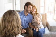 Saleswoman giving apartment keys to new owners. Happy husband and wife receiving key of their future property Royalty Free Stock Photos