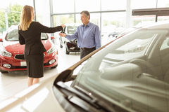 Saleswoman giving car keys while shaking hand of a client Royalty Free Stock Photo