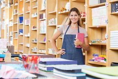 Saleswoman With Hand On Hip Holding Book Royalty Free Stock Images