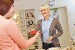 Saleswoman handing jewelry Royalty Free Stock Images